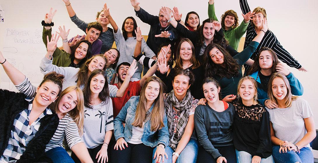 Jóvenes estudiantes de Mondragon Unibertsitatea en grupo con brazos abiertos